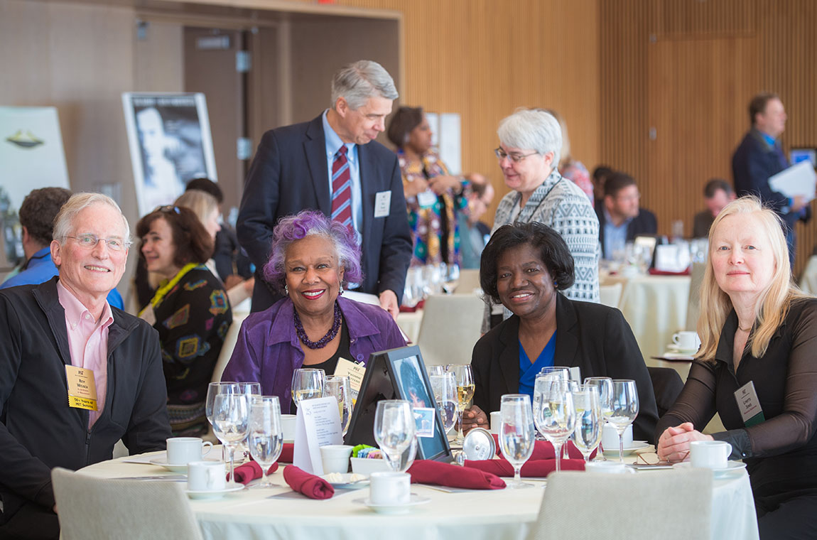 Seated (l-r): 50-year achiever Roy Welsh, QCC President Yvonne Gittens, Beverley Kerr, and Lynette Jones. Background: Lincoln Lab Director Eric Evans and MIT Museum Director of Collections Debbie Douglas