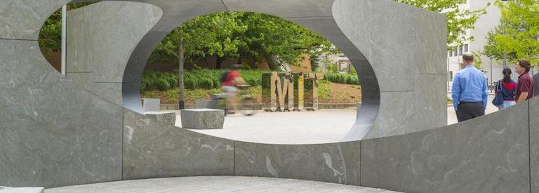 Collier Memorial, with passers-by and metal MIT name statue in frame.